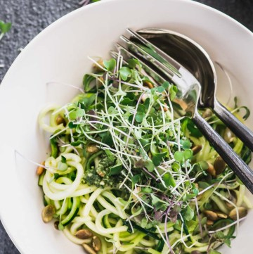 Zucchini noodles in a cream bowl topped with basil almond pesto and micro greens