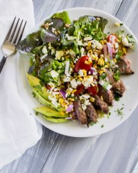Overhead shot of salad with grilled steak, avocado slices and grape tomatoes