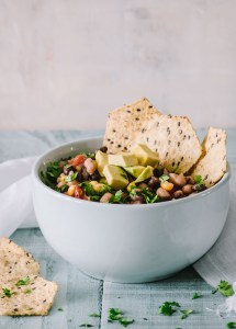 Healthy Cowboy Caviar in a light blue bowl with multigrain tortilla chips