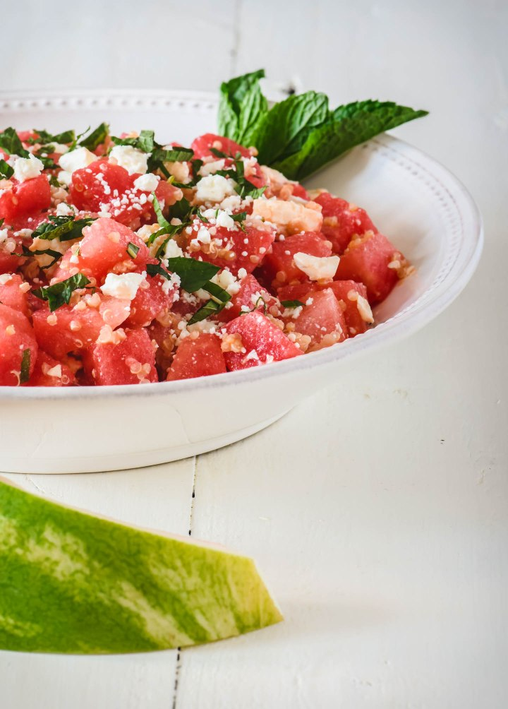 Watermelon salad topped with quinoa, feta and fresh mint leaves