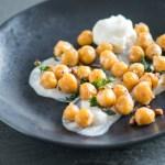 Pan roasted chickpeas on a yogurt base on a black salad plate