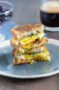 Egg, cheese and pesto sandwich halves stacked on a blue plate