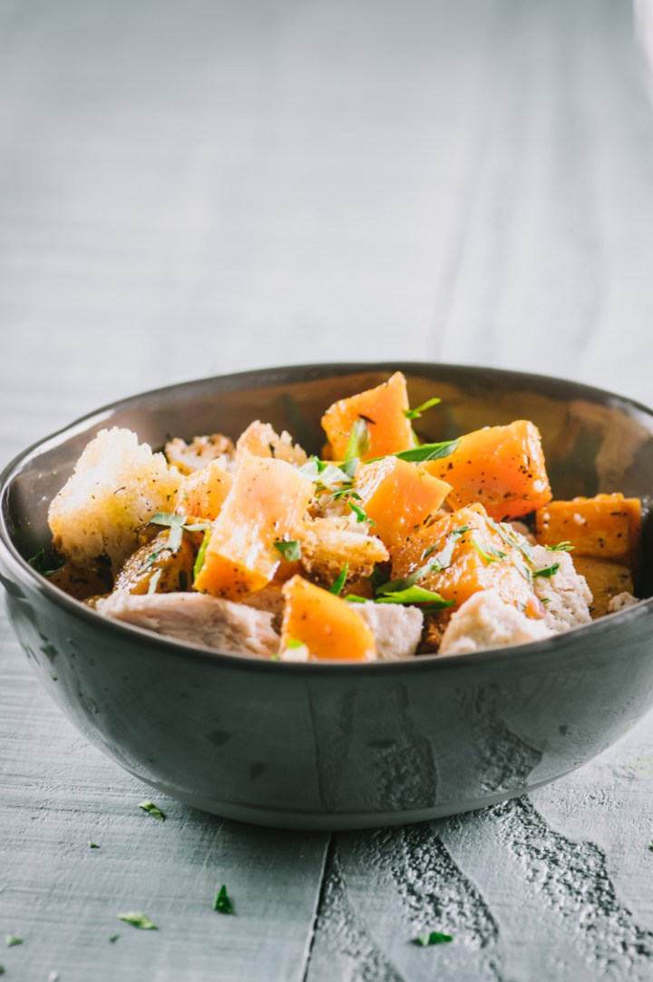 Close up of butternut squash, chicken and croutons in a dark bowl