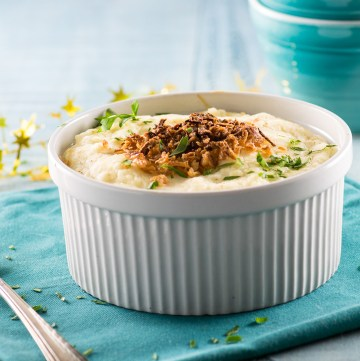 Mashed potatoes topped with crispy onions in a casserole dish
