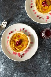 Overhead shot of two butternut squash tarts on cream plates