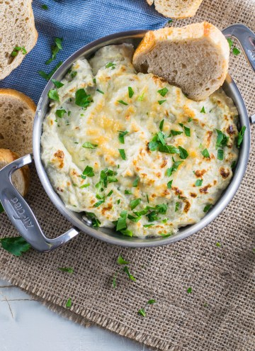 Hot Artichoke Crab Dip in a mini gratin dish with crostini for dipping.