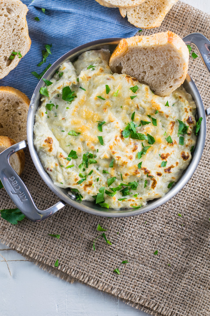 Hot Artichoke Crab Dip in a mini gratin pan with a slice of toasted bread