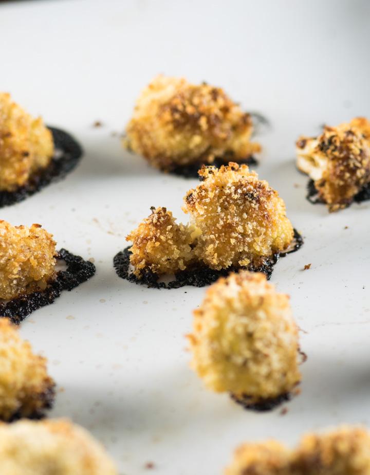 Individual crispy roasted cauliflower florets on a baking sheet