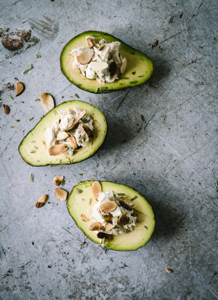 Three avocados stuffed with chicken salad on a light grey background