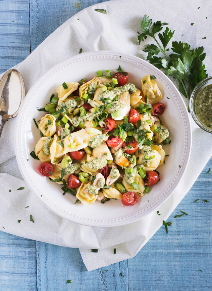 Overhead shot of tortellini pasta salad topped with bright red tomatoes and a pesto dressing.