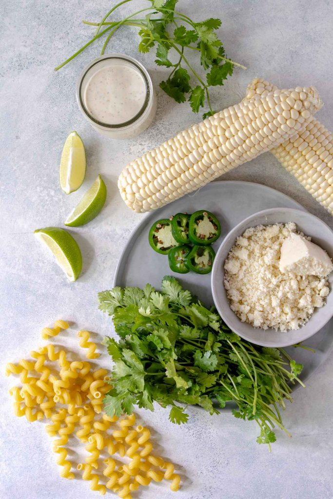 Pasta salad ingredients - corn on the cob, lime wedges, cilantro, dressing and pasta