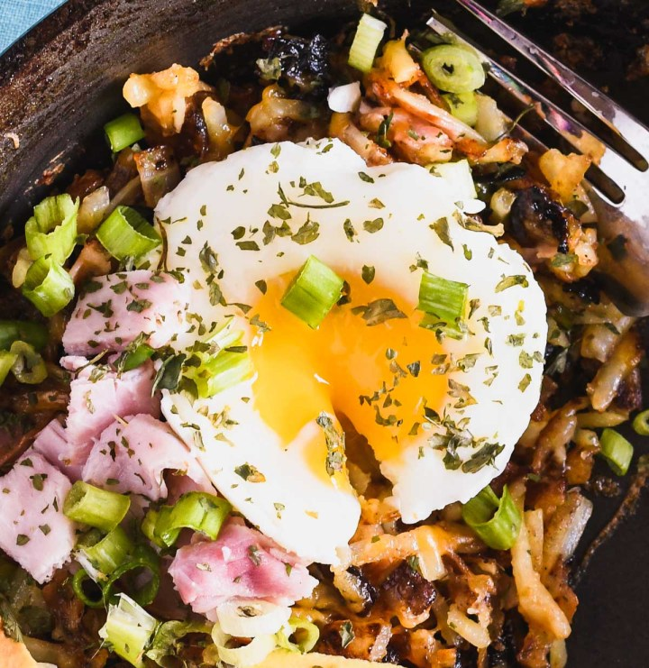 Close up of a poached egg on top of a pan of breakfast hash