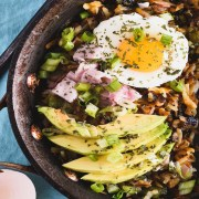 Skillet filled with hash browns, ham, sliced avocado and a poached egg