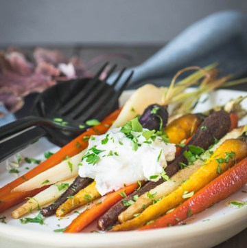 Tri-color roasted carrots on a cream plate