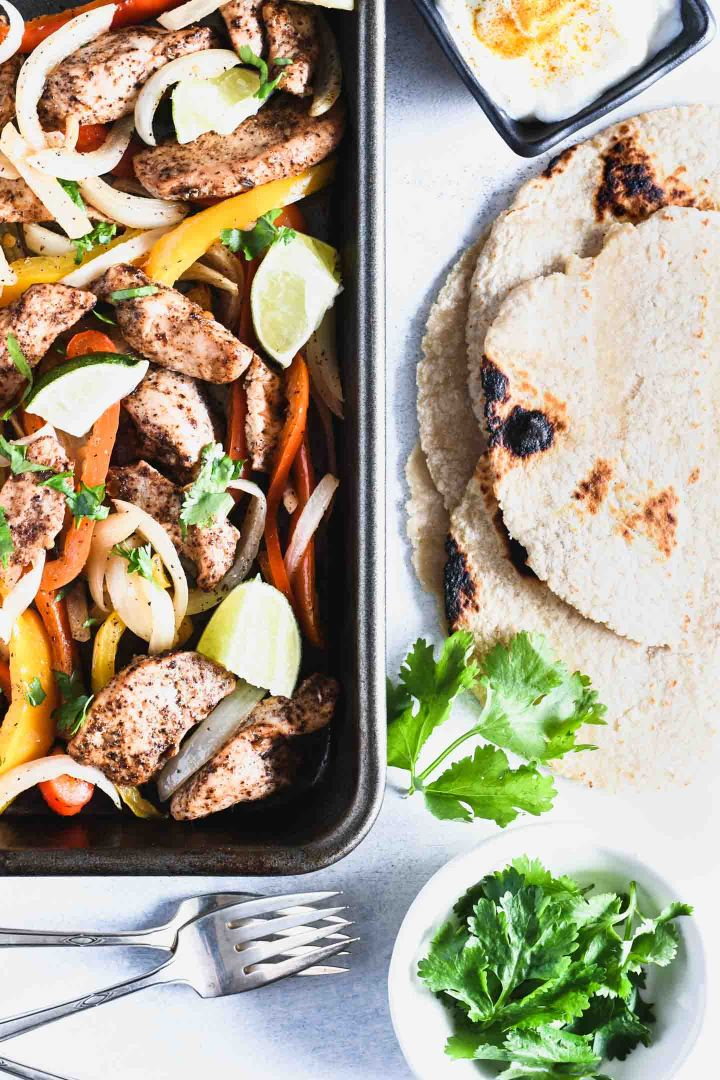 Chicken and vegetables for fajitas on a sheet pan with corn tortillas and cilantro on the side.