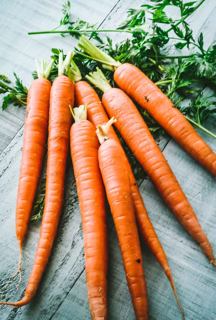 Raw carrots with tops partially chopped off on light teal background