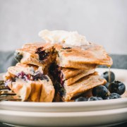 Stack of blueberry protein pancakes with a bit cut out.
