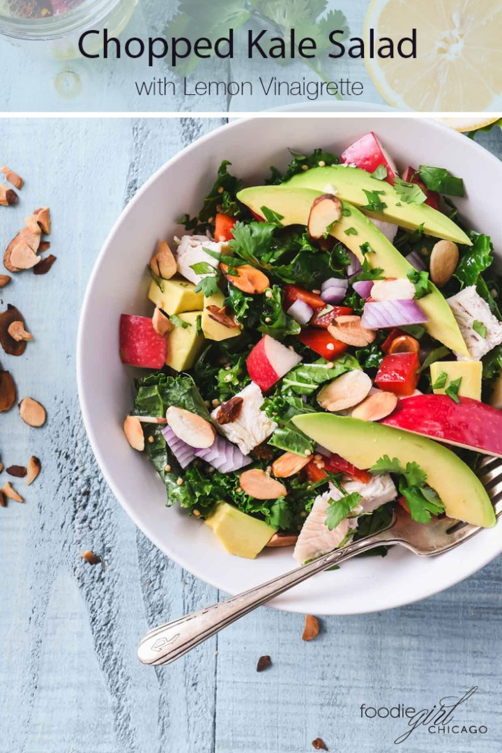 A chopped kale salad topped with sliced avocados, apples and almonds in a cream bowl