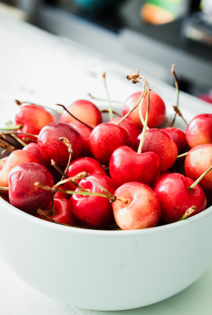 bright red cherries in a light blue bowl