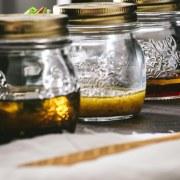Three types of homemade vinaigrette in small mason jars