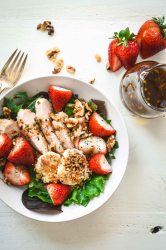 Salad topped with grilled chicken, strawberries and baked goat cheese