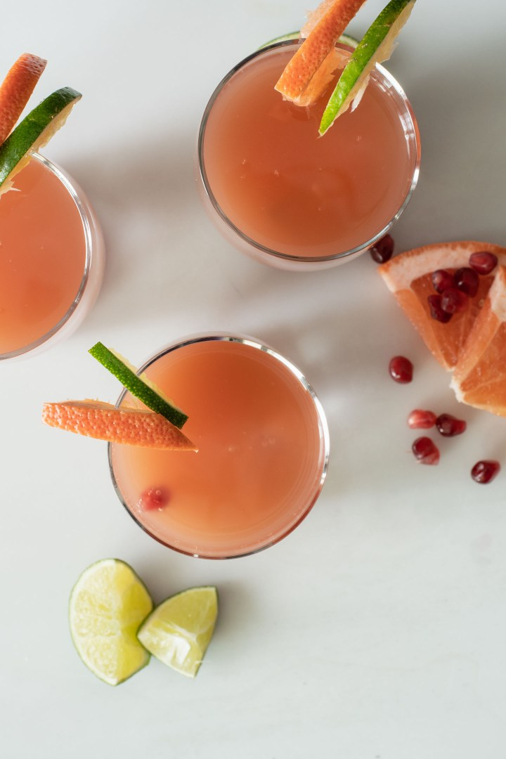 Three glasses with pomegranate paloma cocktail from overhead