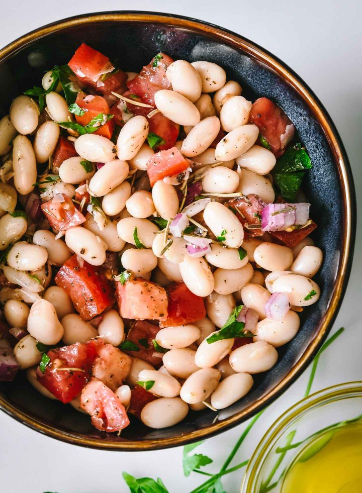 Close up of white beans topped with diced tomatoes, red onion and herbs