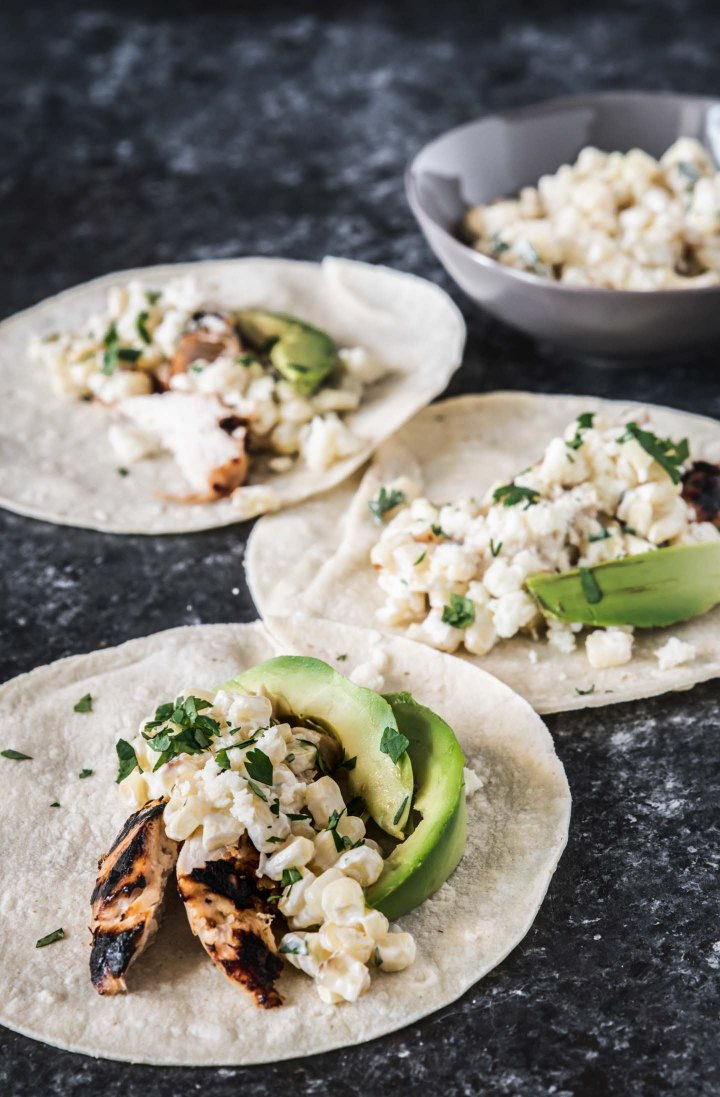 Three grilled lime chicken tacos topped with Elotes