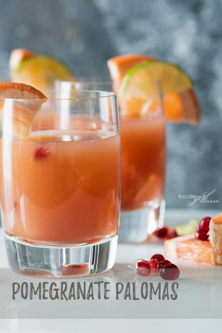 Three pomegranate paloma cocktails with grapefruit slices on the side