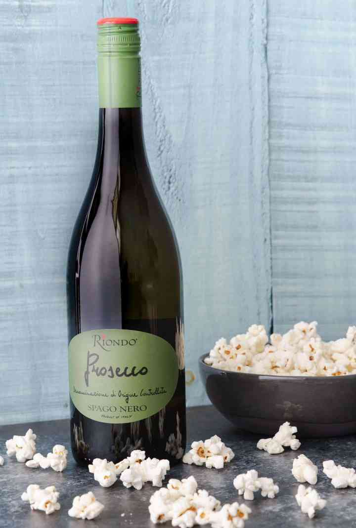 Riondo prosecco bottle with popcorn bowl and scattered popcorn