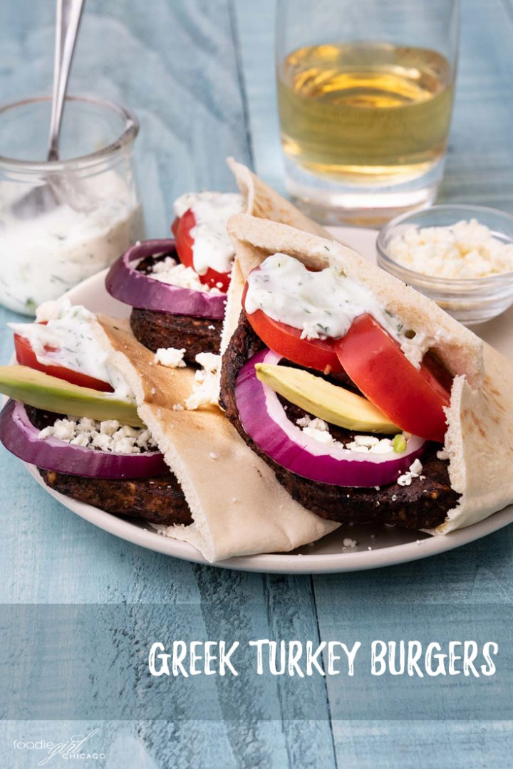 Three veggie burgers in pita pockets with Greek-inspired toppings