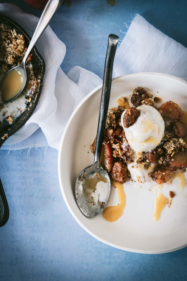 Apple crisp served on a cream plate and drizzled with caramel sauce
