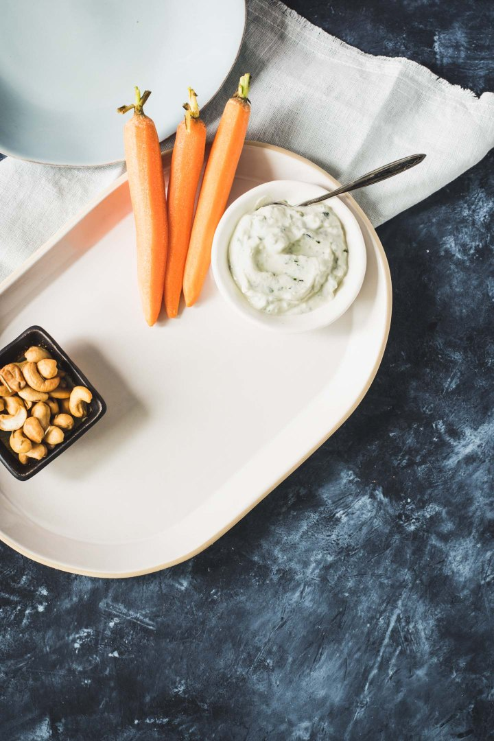 Beginnings of a snack dinner with dip, carrots and cashews on a platter