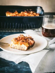 Slice of breakfast casserole on a plate with entire casserole in background.