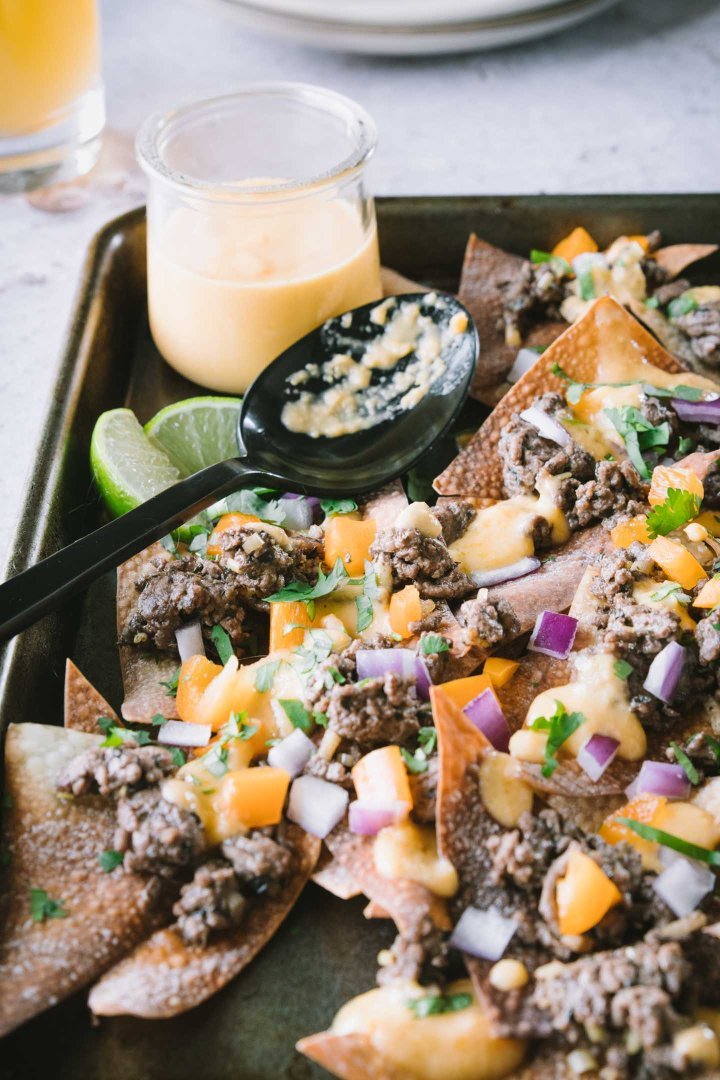 Close up shot of wonton nachos topped with lemongrass beef and beer cheese sauce