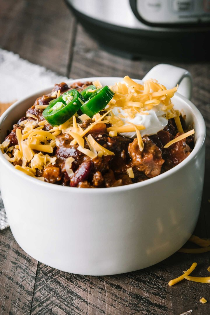 Beef chili in a cream bowl topped with sour cream and shredded cheddar cheese