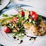 Chicken milanese on a white plate topped with chrrey tomatoes, arugula and avocado
