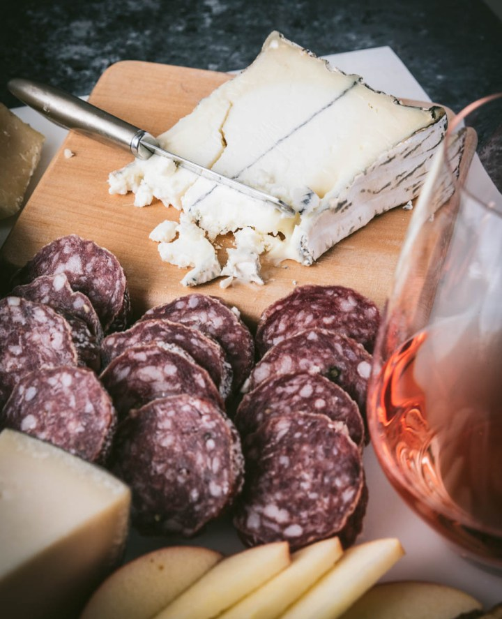 Truffle Tremor cheese on a wood board with salami and a glass of Rose
