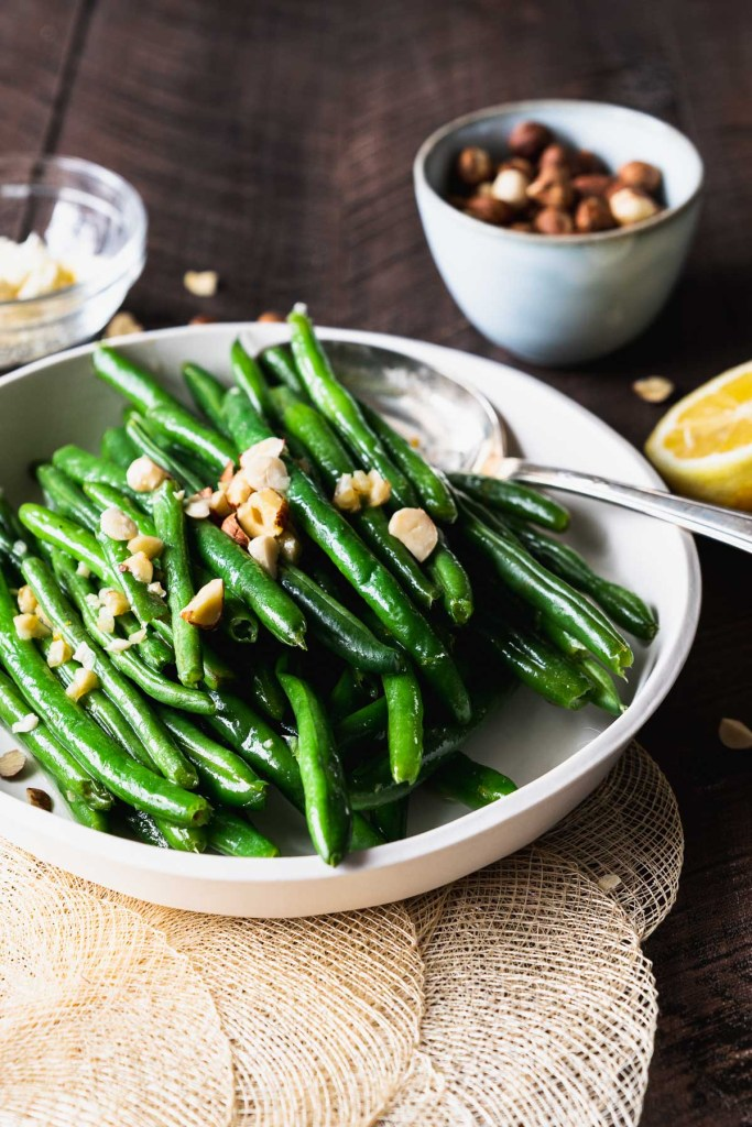 Green beans on a white plate with a silver serving spoon