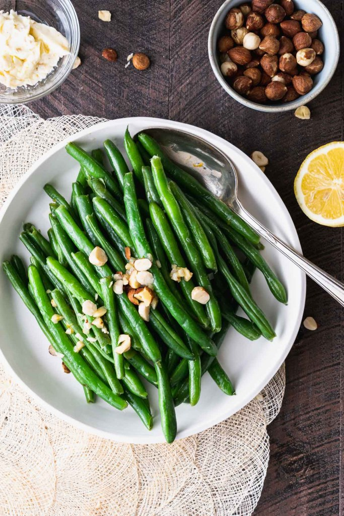Green beans topped with hazelnut compound butter in a white dish