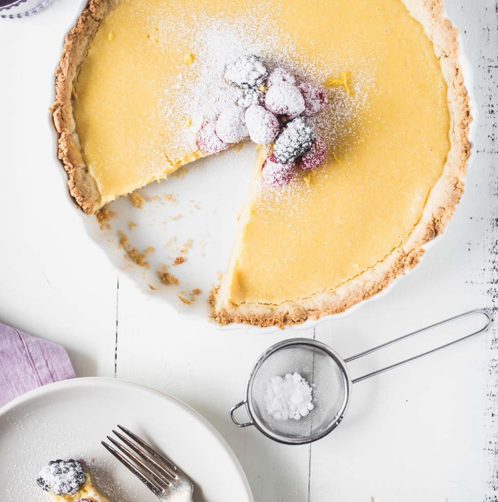 Overhead photo of lemon tart topped with berries with a slice cut out