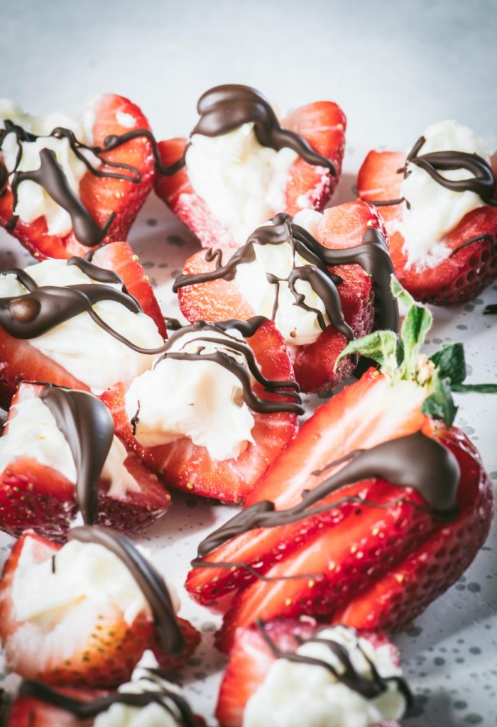 Close up of strawberry halves stuffed with cheesecake and drizzled with dark chocolate