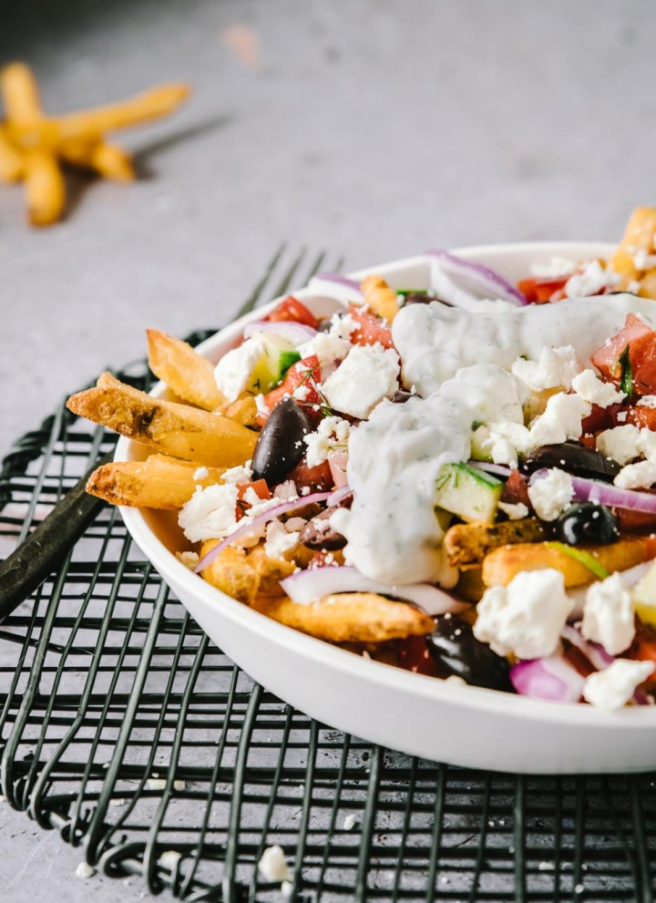 Plate of oven baked french fries topped with tomatoes, peppers, red onion, feta and tzatziki sauce