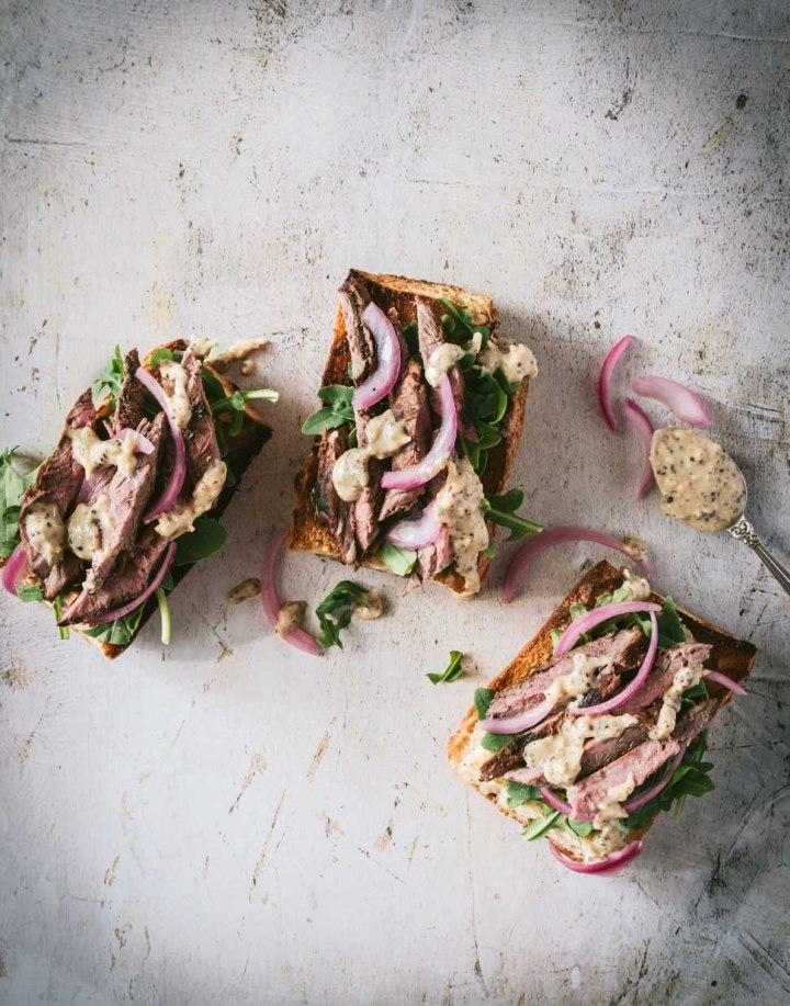 Three open faced sandwiches topped with grilled flank steak, bright pickled red onions and parmesan sauce