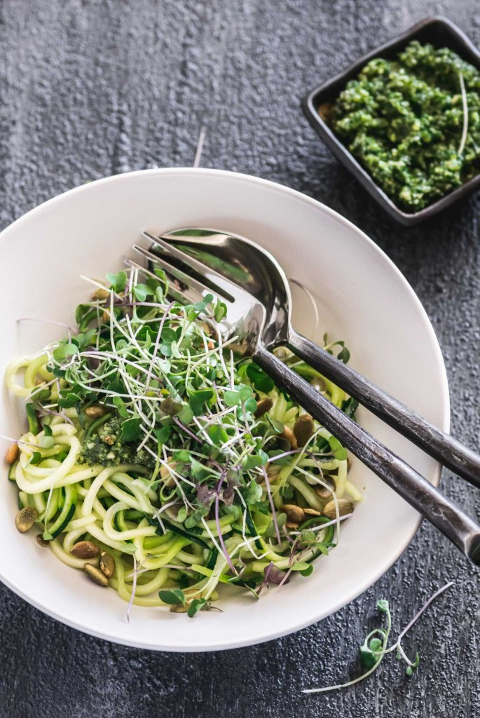 Overhead shot of zucchini noodles in a white bowl topped with pesto and micro greens