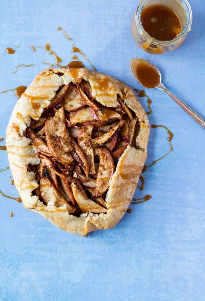 Whole apple galette drizzled with caramel sauce on a blue background