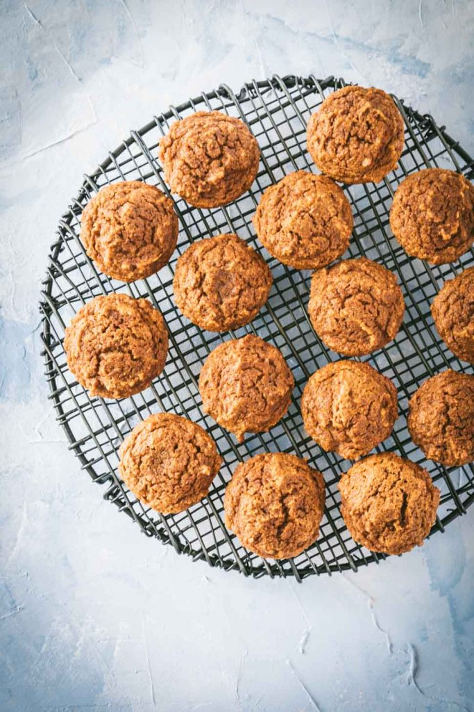 Overhead photo of pumpkin muffins on a round black cooling rack