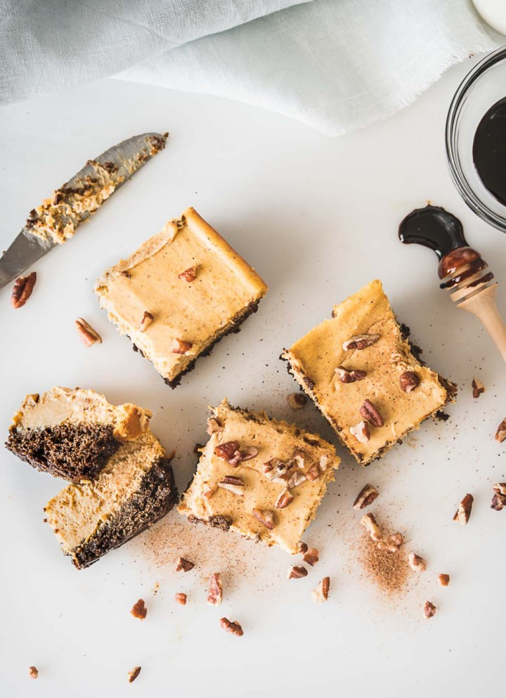 Overhead shot of pumpkin cheesecake bars topped with pecan pieces
