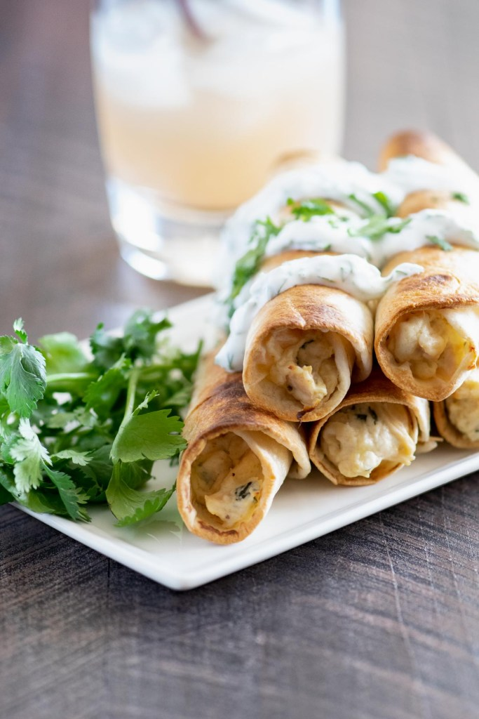 Stack of baked chicken flautas on a white tray
