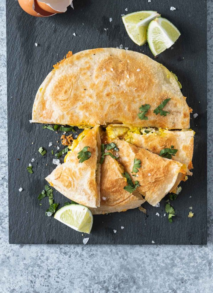 Breakfast quesadilla on a black slate board shot from overhead
